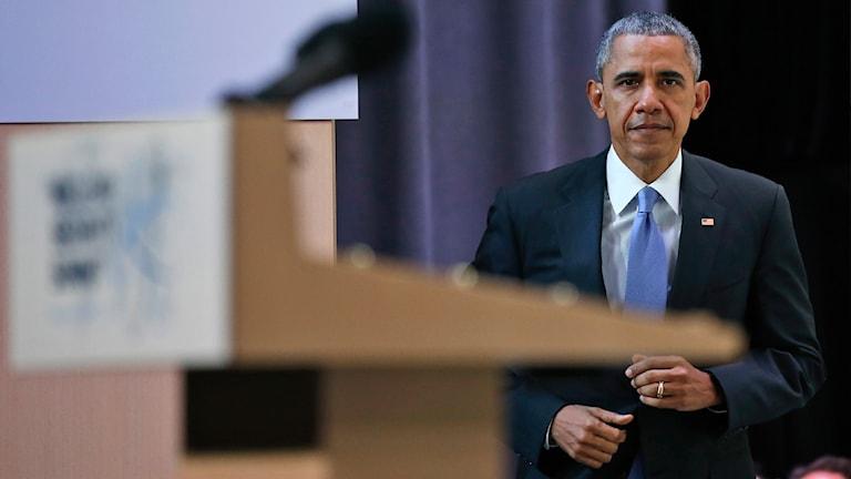 Barack Obama går mot ett podium.