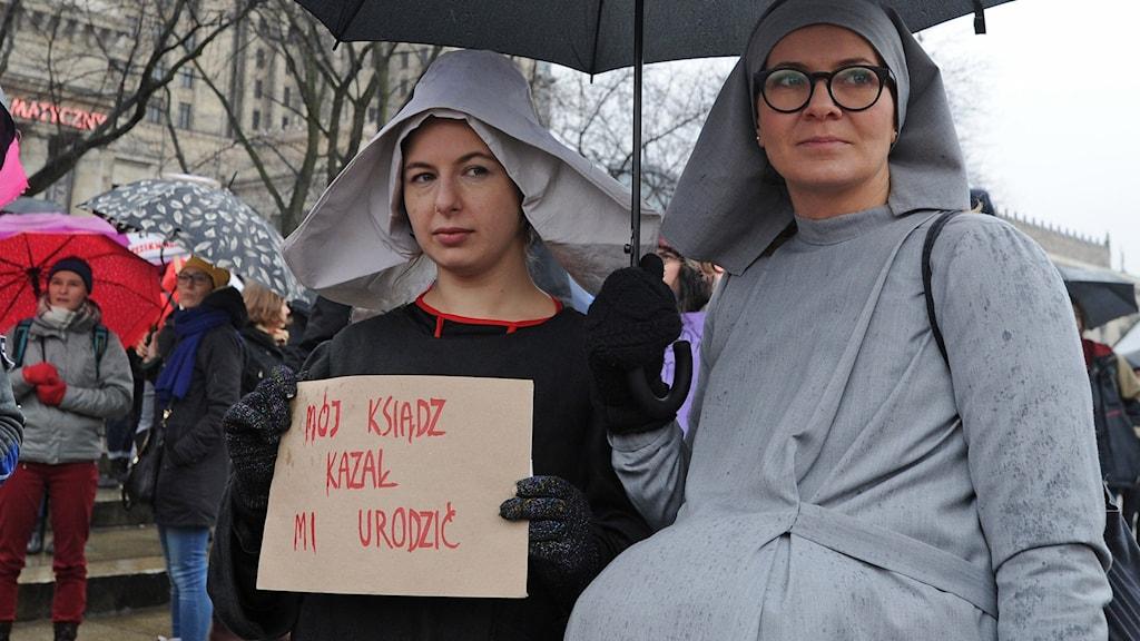 Kvinnor i nunnekläder håller upp plakat och paraply.