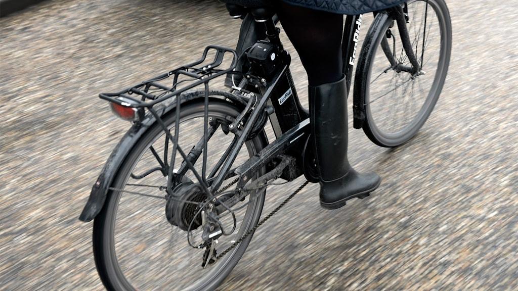 Kvinna cyklar på elcykel.