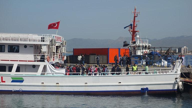 Passagerarbåt med migranter ligger vid en kaj