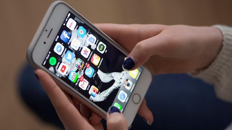 Ett par händer som håller i en Iphone