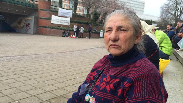 Bilden visar Alexandrina Brebenel, från Rumänien, som sitter på trapporna vid Stadshuset i Malmö och demonstrerar med kravet att kommunen ska anvisa en laglig boplats. I bakgrunden syns demonstranternas banderoller. Foto: Anna Bubenko/Sveriges Radio.