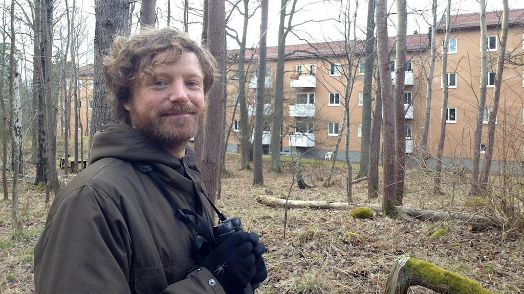 En man står i en skogsdunge nära bostadshus.
