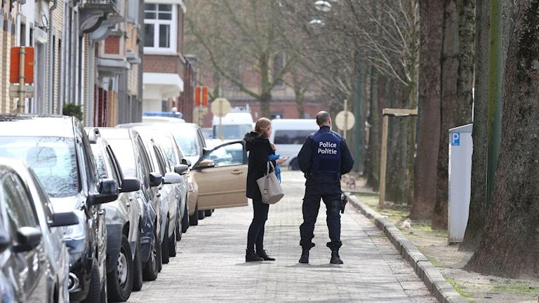 Polis pratar med en boende under tillslaget i förorten Etterbeek i Bryssel.