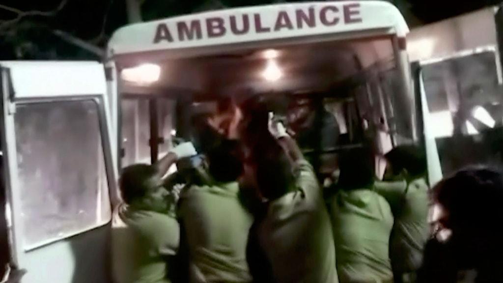 Män i gröna uniformer hjälper människor in i en ambulans