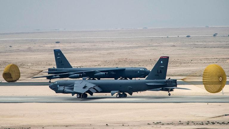 Två grå bombplan med gula fartskärmar uppfällda bakom sig står i ökenlandskap.