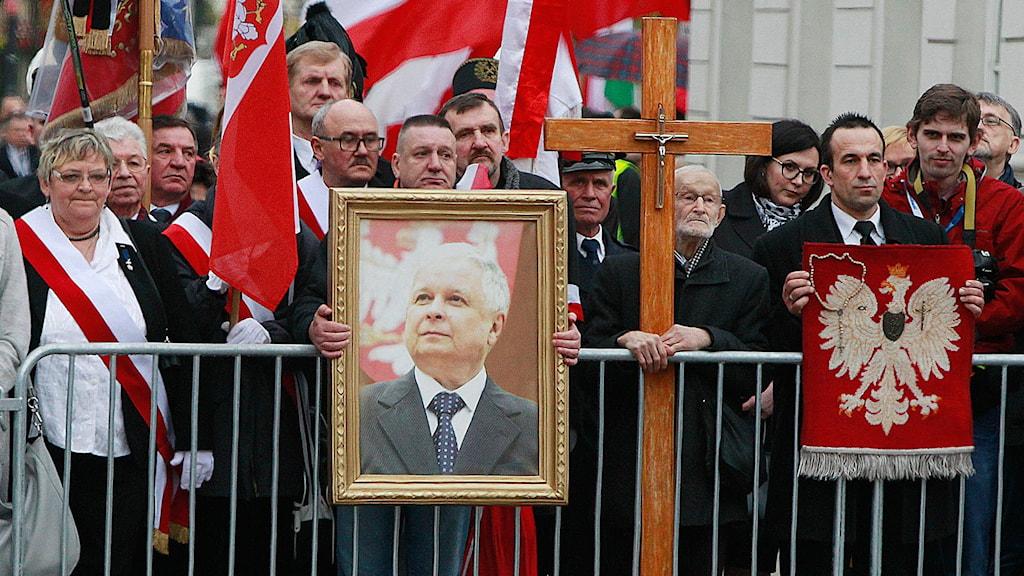 Folksamling bakom kravallstaket håller upp flaggor och en tavla i guldram föreställande ett porträtt på en äldre man