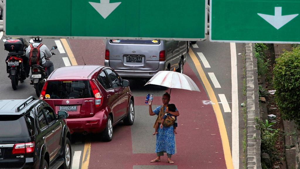 En kvinna med barn på en väg i Jakarta, Indonesien.