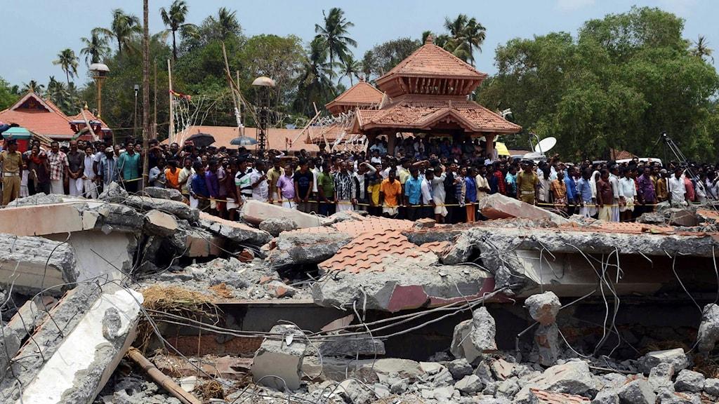 Människor tittar på ett raserat tempel efter en stor brand.
