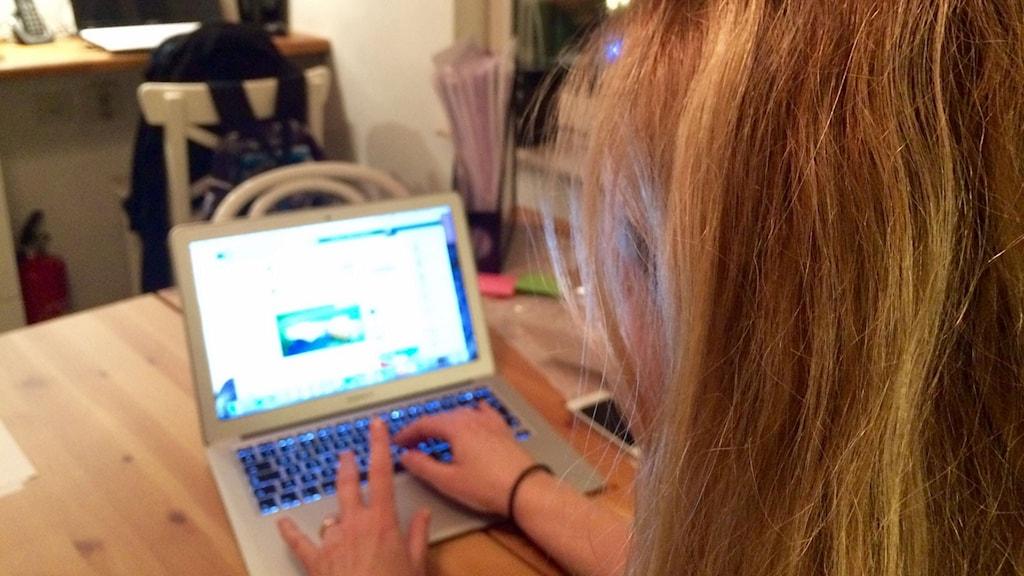 Kvinna vid dator, fotograferad bakifrån. Foto: Katarina Helmerson/Sveriges Radio.