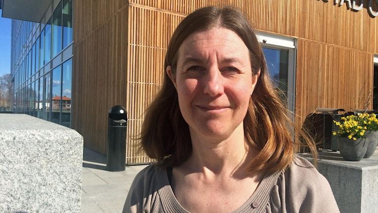 Kvinna med axellångt hår framför byggnad.