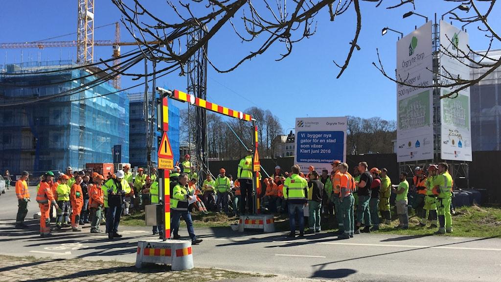 Människor i gula och orangea kläder framför en byggarbetsplats.