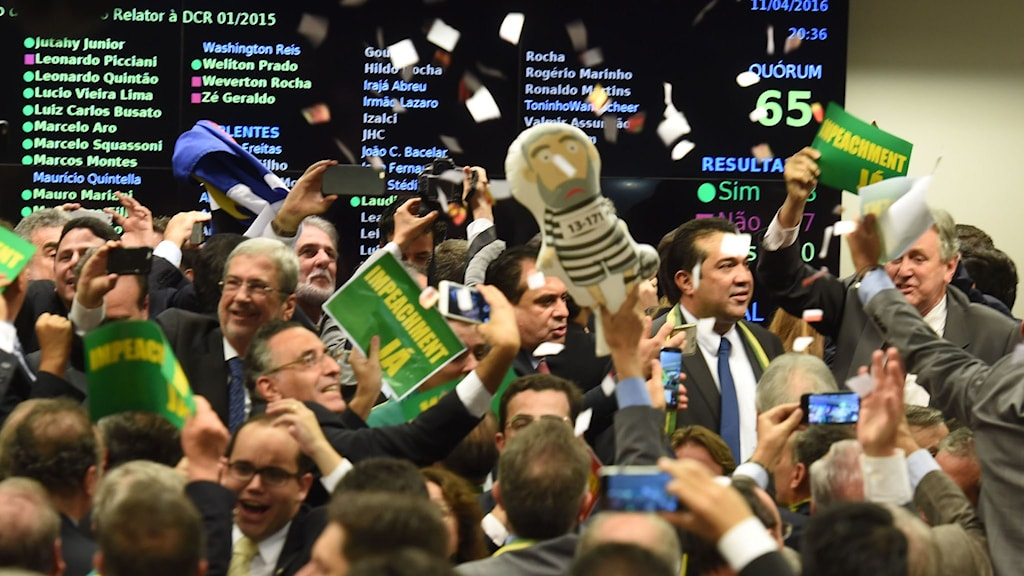 Glada människor som håller upp plakat.