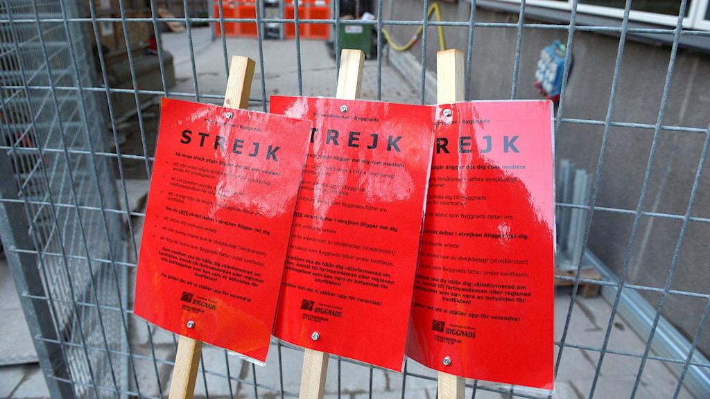 """Röda skyltar med texten """"Strejk""""."""