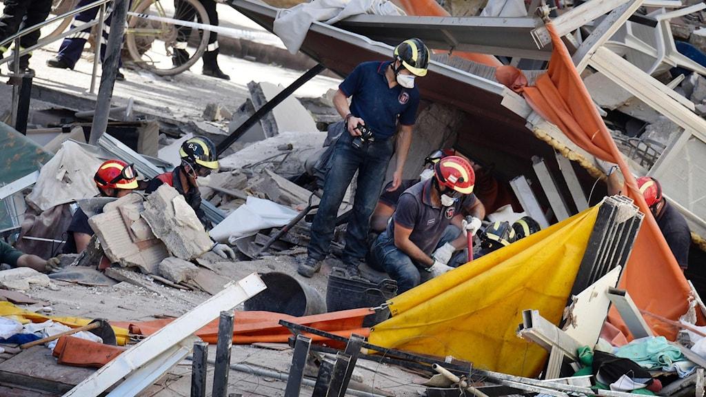 Räddningsarbetare vid den kollapsade byggnaden.