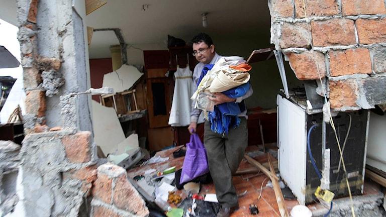 En man letar efter sina saker i ett jordskalvskadat hus i Pedernales.