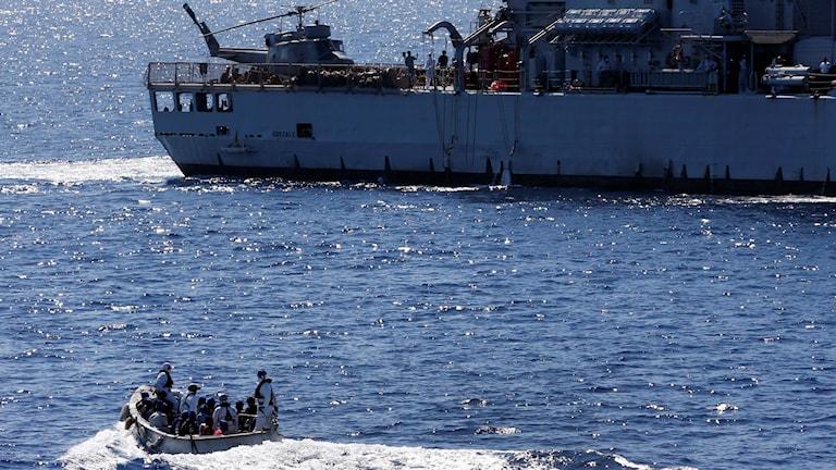 Mindre gummibåd och större räddningsfartyg på soligt medelhav