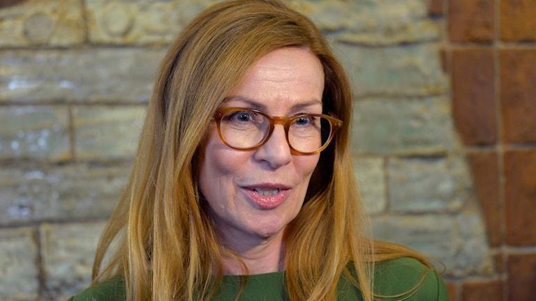Kvinna med glasögon, långt hår och grön tröja.