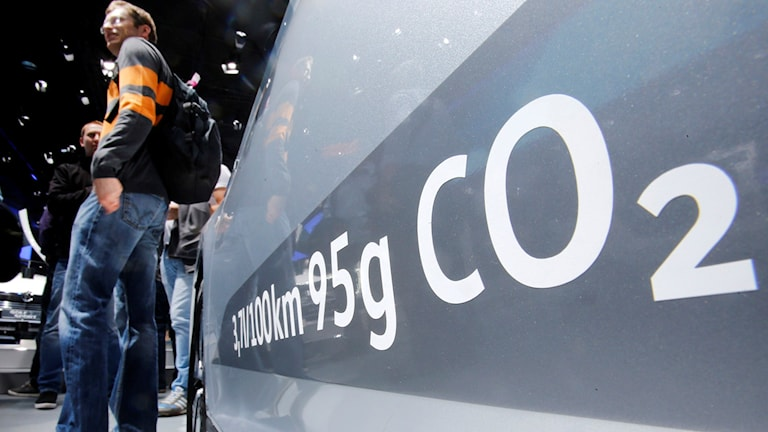 En man står bredvid en bil vars koldioxidutsläpp står skrivet på sidan av fordonet.