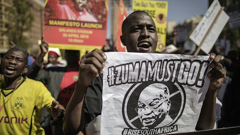 """Man med affisch med texten """"Zuma Must Go!"""" under protester mot Jacob Zuma i Johannesburg, Sydafrika"""