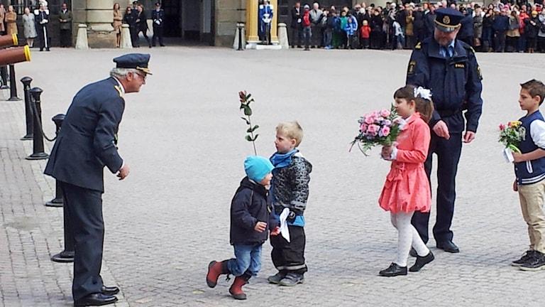 Här är två olika bilder, från 2013 när kungen får blommor av barn på födelsedagen.
