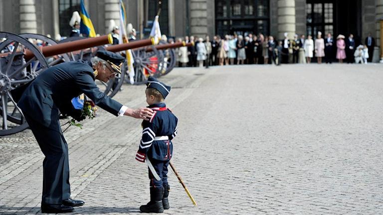 Kung Carl Gustaf tar emot blommor av en liten pojke på yttre borggården.