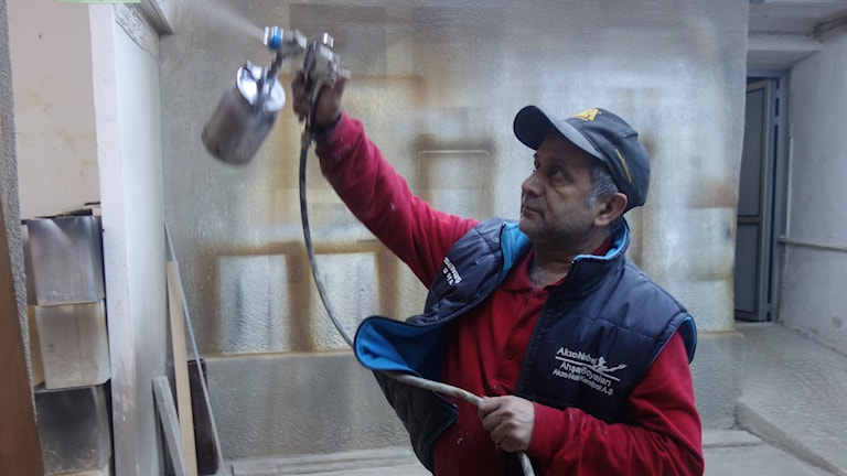 Hantverkaren Suleyman Baris målar ett skåp. Han vill inte resa till EU.