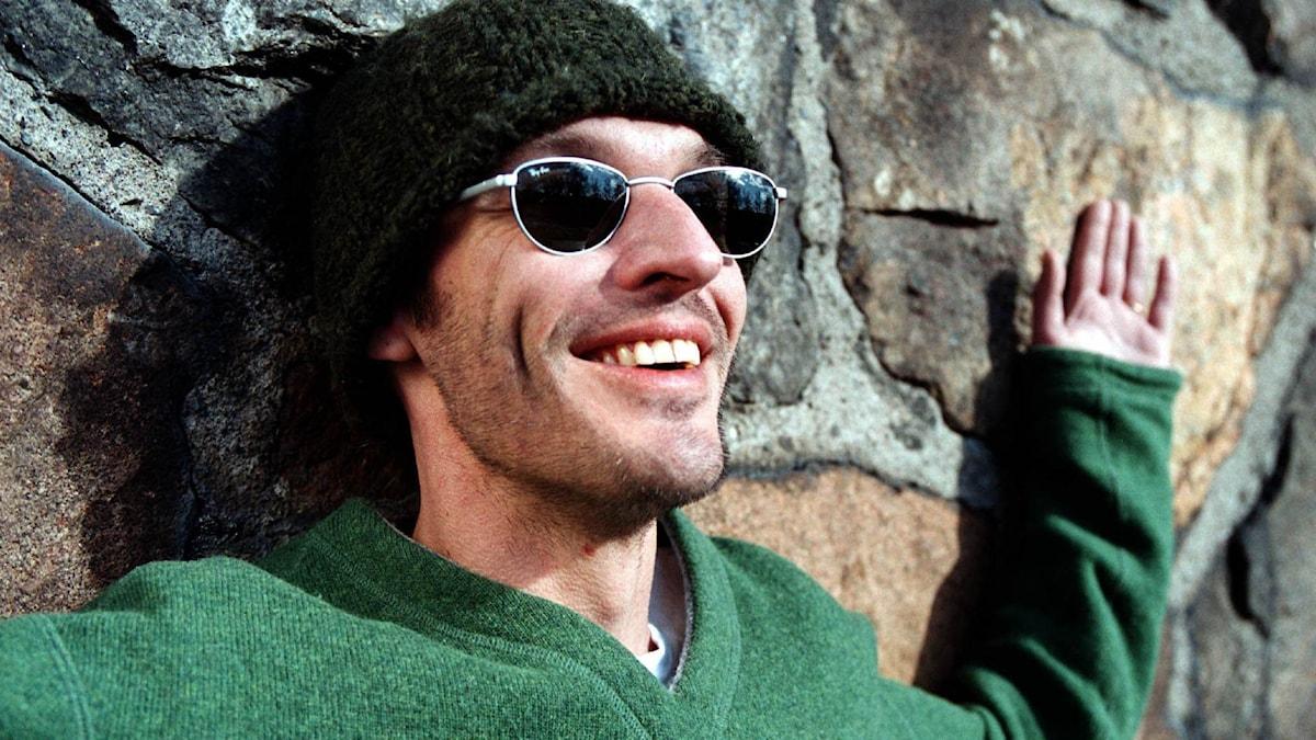 Man i mössa och solglasögon ler och slår ut med armarna.