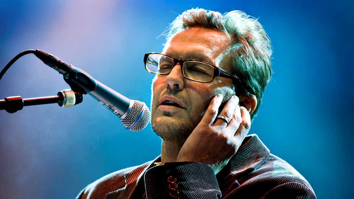 Man sjunger in i mikrofon, sluter ögonen. Blå bakgrund.