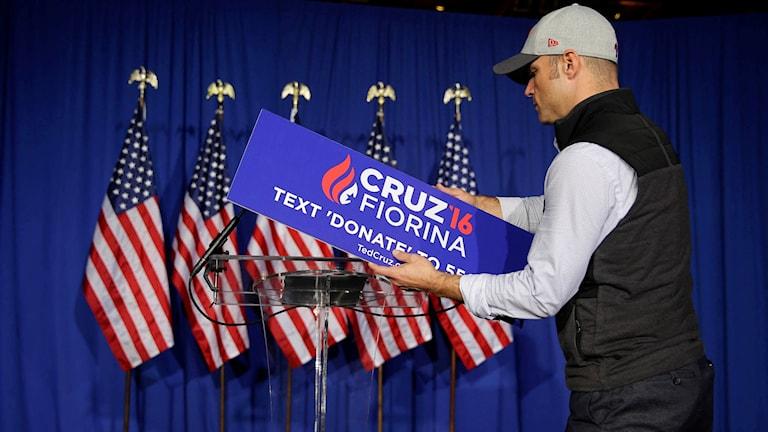 En kampanjarbetare plockar ner skylten.