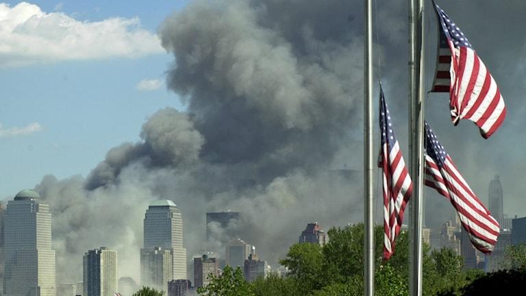 Amerikanska flaggor på halv stång syns vajja framför röken som stiger över Manhattan.