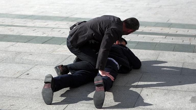 Man med vapen brottas ner av polis utanför rättssalen.