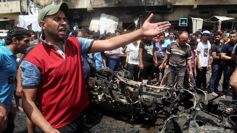 Människor i Bagdad där en bilbomb exploderat på morgonen.
