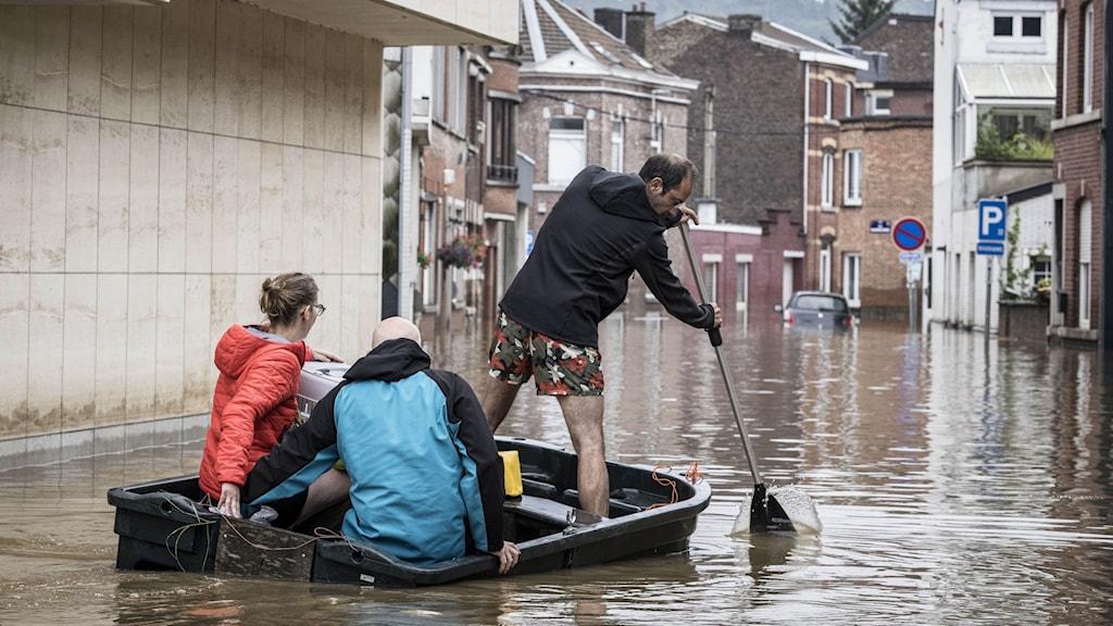En man ror sin båt genom de översvämmade gatorna.