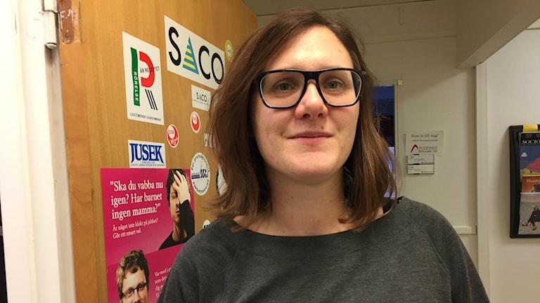 Bilden visar Katrin Skatt Gåvertsson, ordförande för akademikerförbundet SSR i Malmö stad. Hon står framför en dörr på fackets expedition. Det är klistermärken på dörren. Foto: Anna Bubenko/Sveriges Radio.
