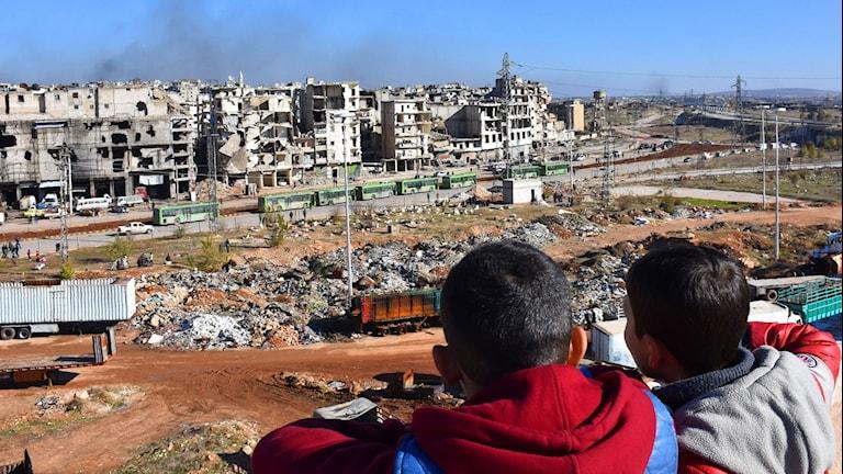 Två små pojkar kollar på gröna bussar som för ut människor från Aleppo