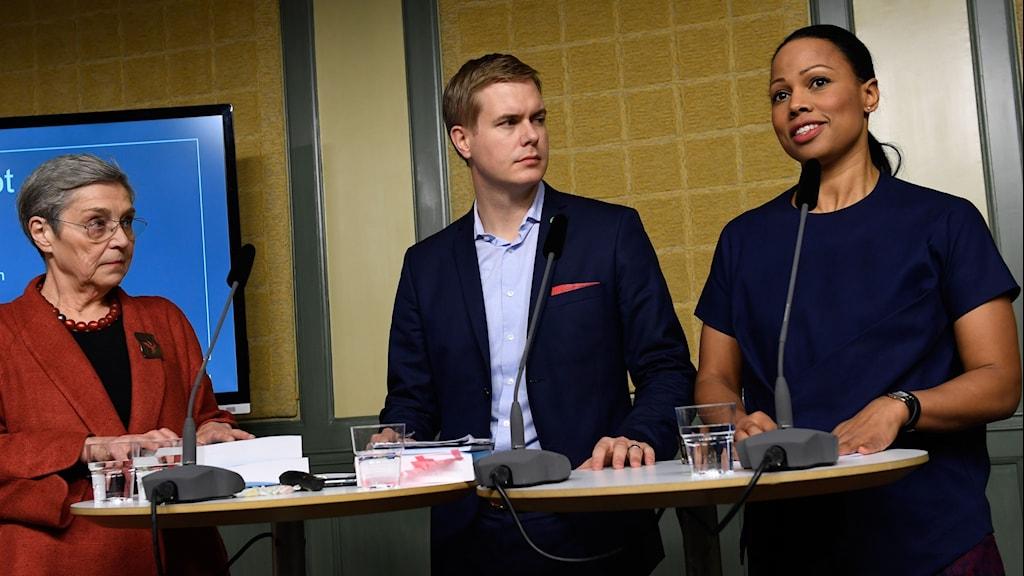 Presskonferens - tre personer står vid två små bord och presenterar utredningen
