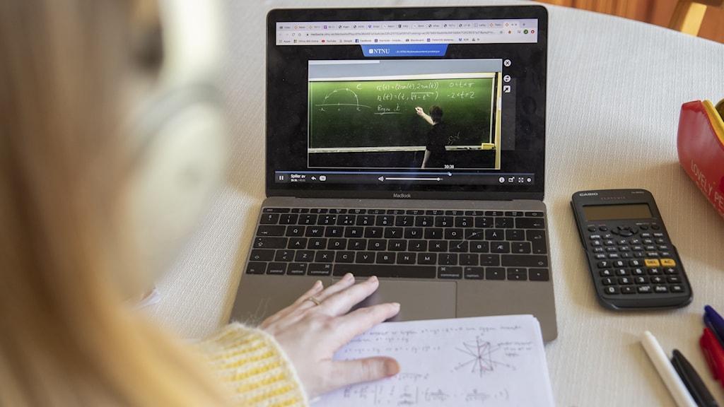 en elev som tittar på en skärm där en mattelektion pågår.