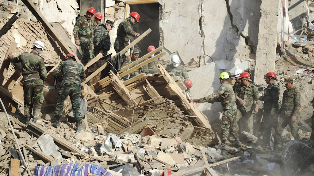 Räddningsarbetare vid ett förstört hus i Nagorno-Karabakh