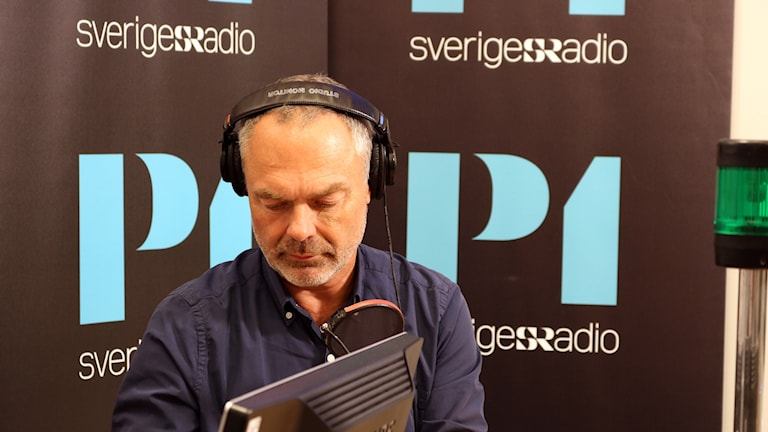 Jan Björklund sitter med hörlurar och mikrofon i studion.