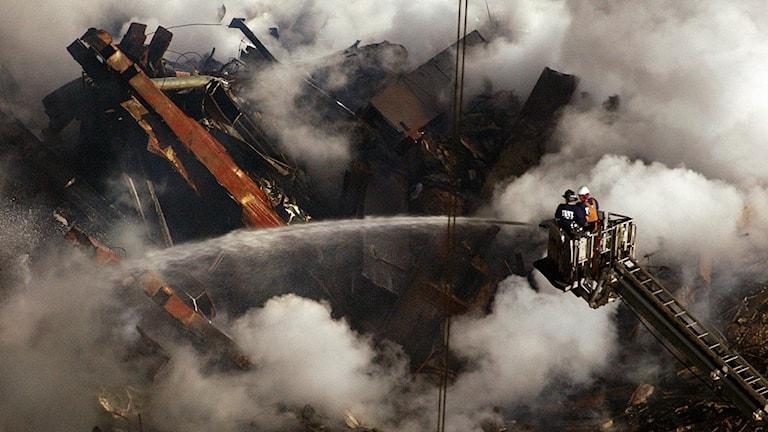 Brandmän släcker resterna av World Trade Center i New York den 11 september 2001.