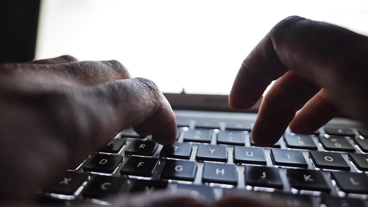 Närbild av händer som skriver på tangentbord i mörk omgivning