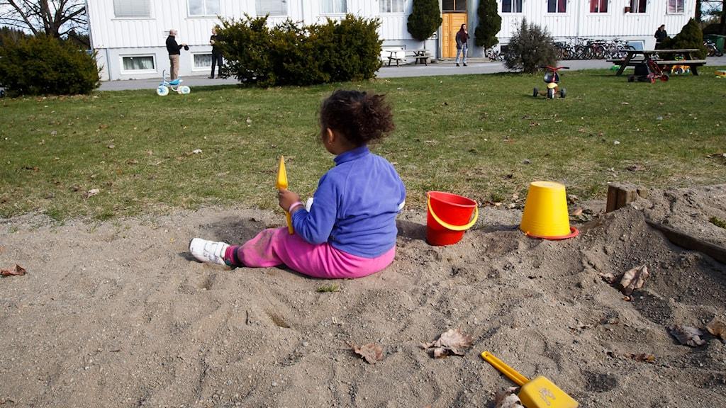 Bilden visar en flicka som leker i sandlådan utanför ett asylboende i Norge.
