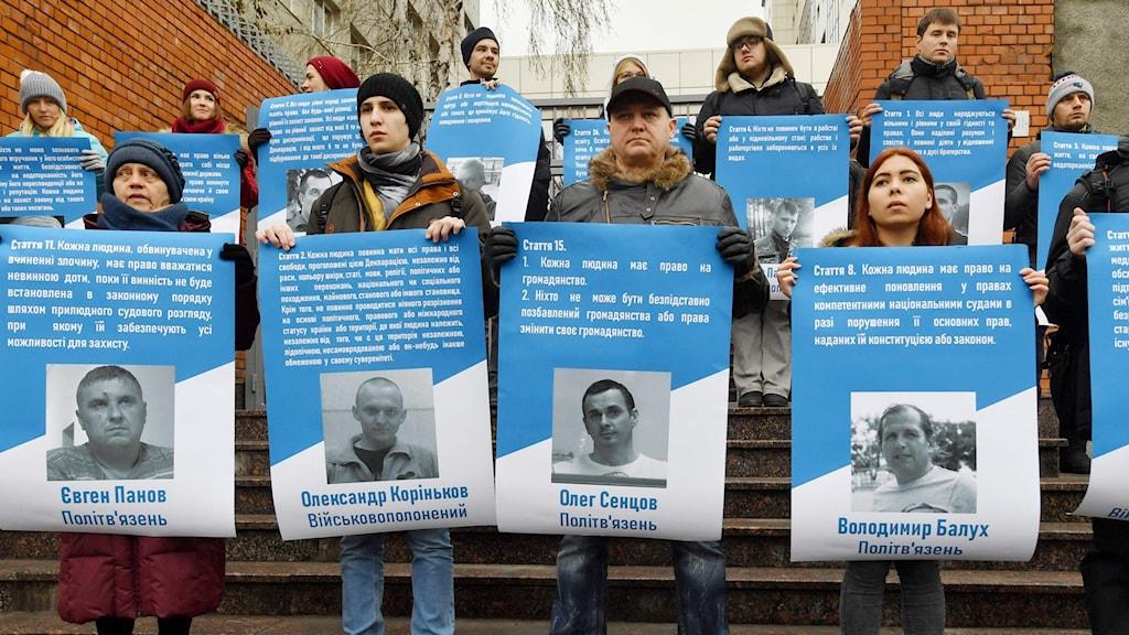 Ukrainska aktivister håller upp bilder på personer som sitter fängslade i Ryssland, bland annat en av de sjömän som togs tillfånga.