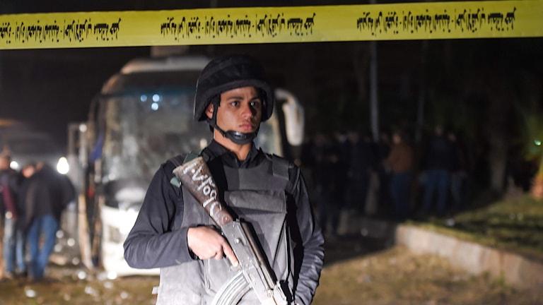Person med vapen framför bussen.