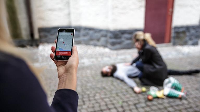 Person ligger på marken, en person sitter bredvid och en person håller en mobiltelefon med en karta över var det finns hjärtstartare