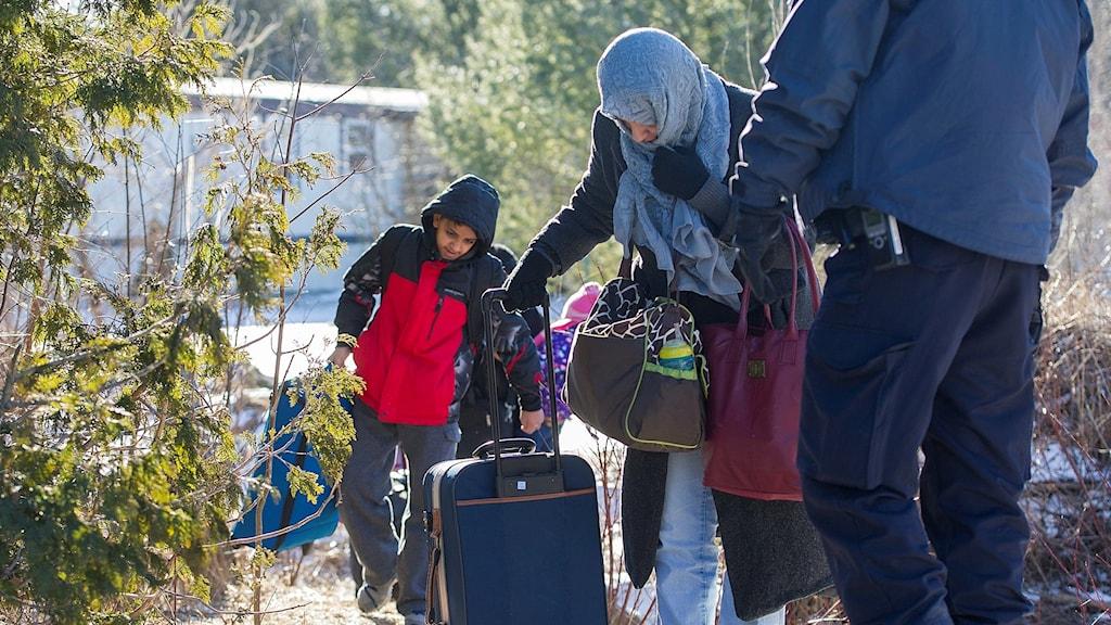 En kvinna och ett barn kommer över gränsen med små kabinväskor där en kanadensisk gränsvakt väntar, tidigare i år.