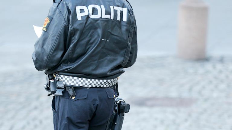 En norsk polis står med ryggen mot kameran.
