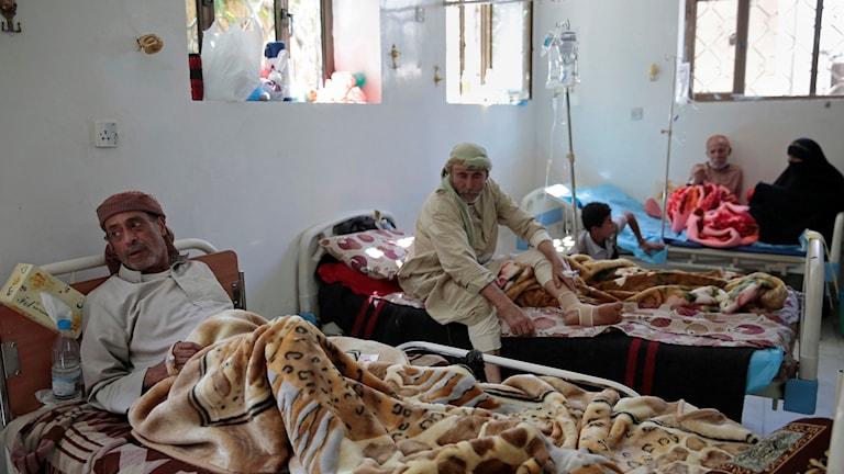 Fyra människor som halvsitter i varsinna sängar i ett rum på ett sjukhus i Jemen.