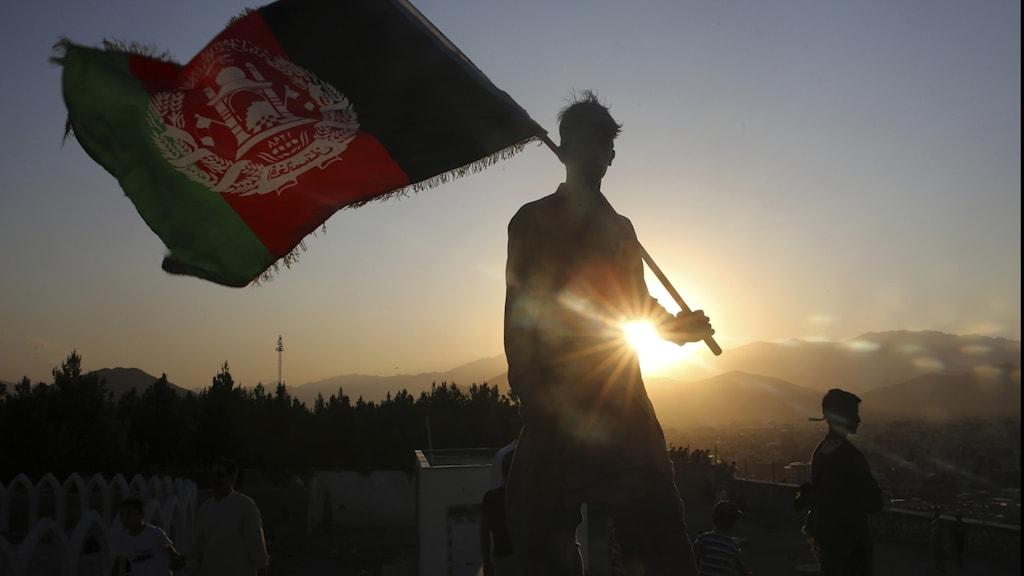 man håller afghansk flagga mot solnedgång